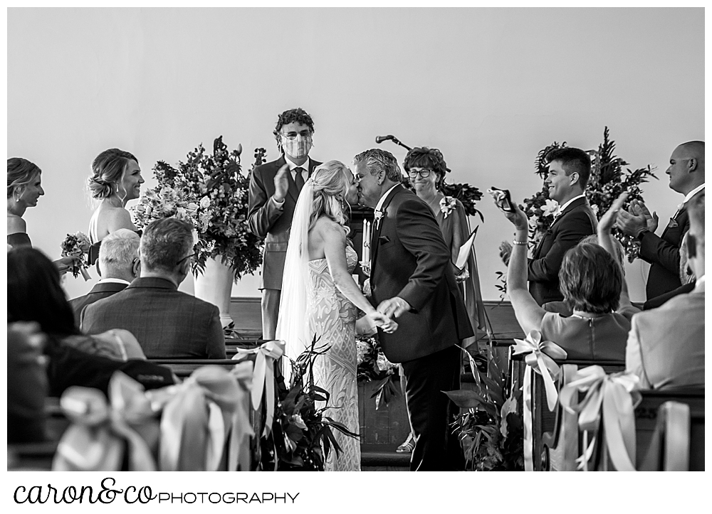black and white photo of a bride and groom's first kiss at the spurwink church cape elizabeth maine wedding ceremony