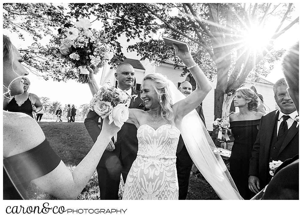 black and white photo of bride with raised arms, smiling