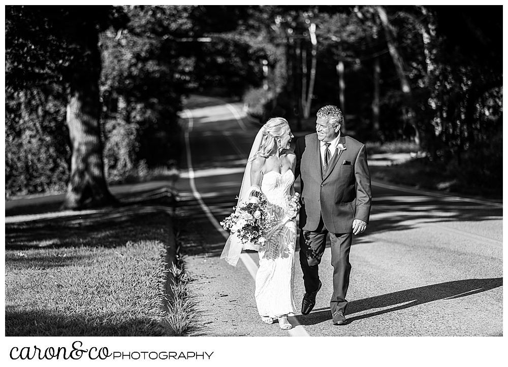 black and white photo of a bride and groom walking along the side of the road