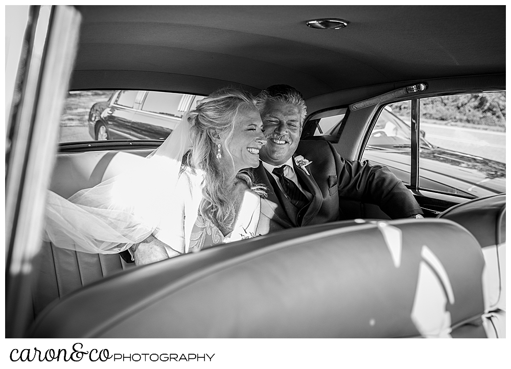 black and white photo of a bride and groom in their getaway car