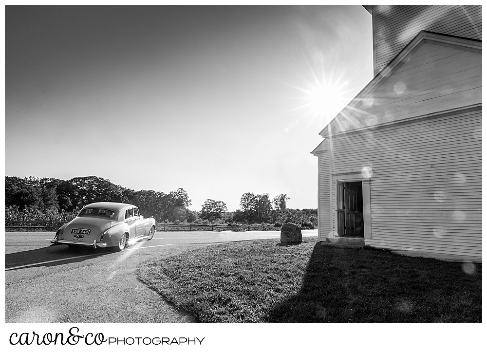black and white photo of a Maine Limousine Service Bentley driving around the corner of the spurwink church, cape elizabeth, maine