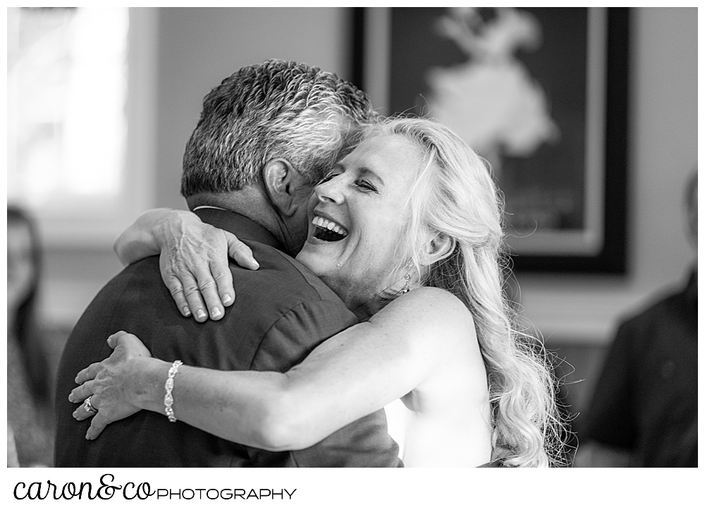 black and white photo of a bride and groom dancing, the bride is laughing