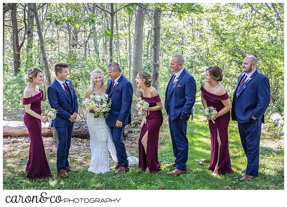 bride and groom with their bridal party in the woods, having fun