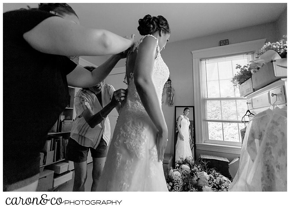 sweet summertime wedding, black and white photo of bride getting into her wedding dress with her mother and matron of honor
