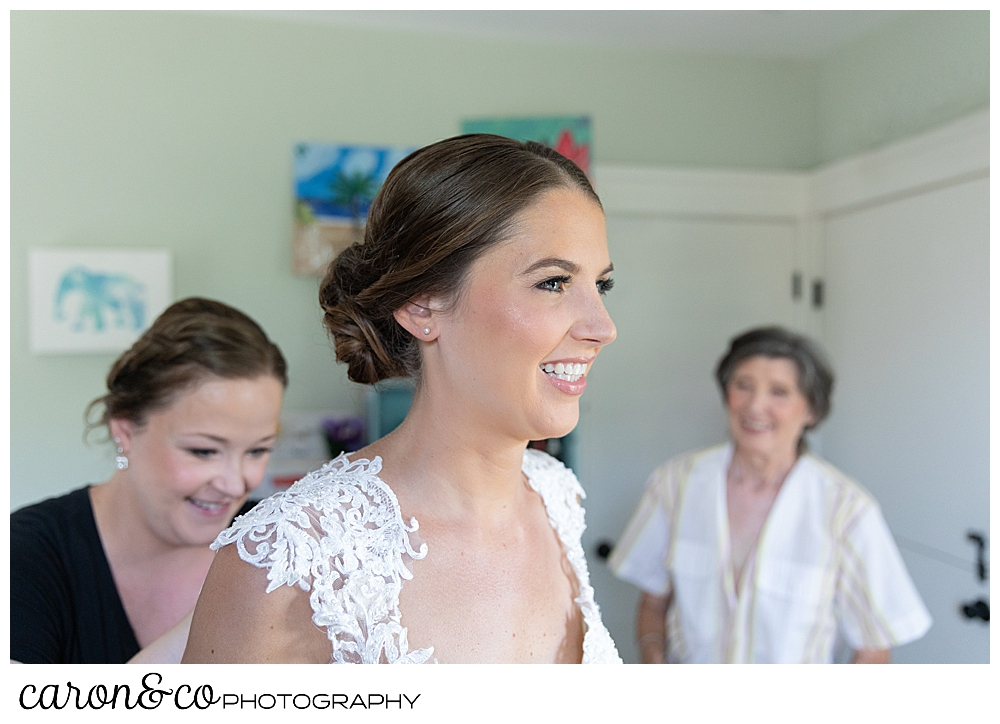sweet summertime wedding bride getting dressed with her mother and matron of honor