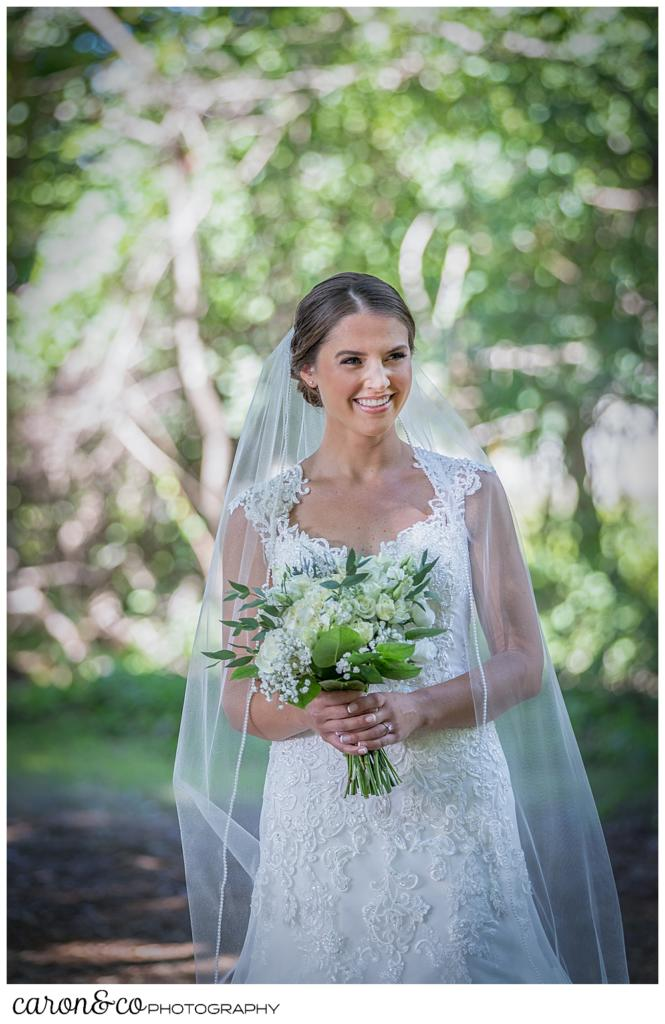 bride in a white wedding dress and veil, holding a green and white bouquet, smiling as the groom walks towards her