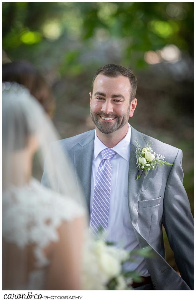 sweet summertime wedding day first look, smiling groom walks toward the bride