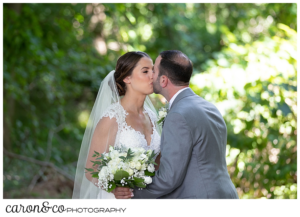 sweet summertime wedding day first look, bride and groom kissing