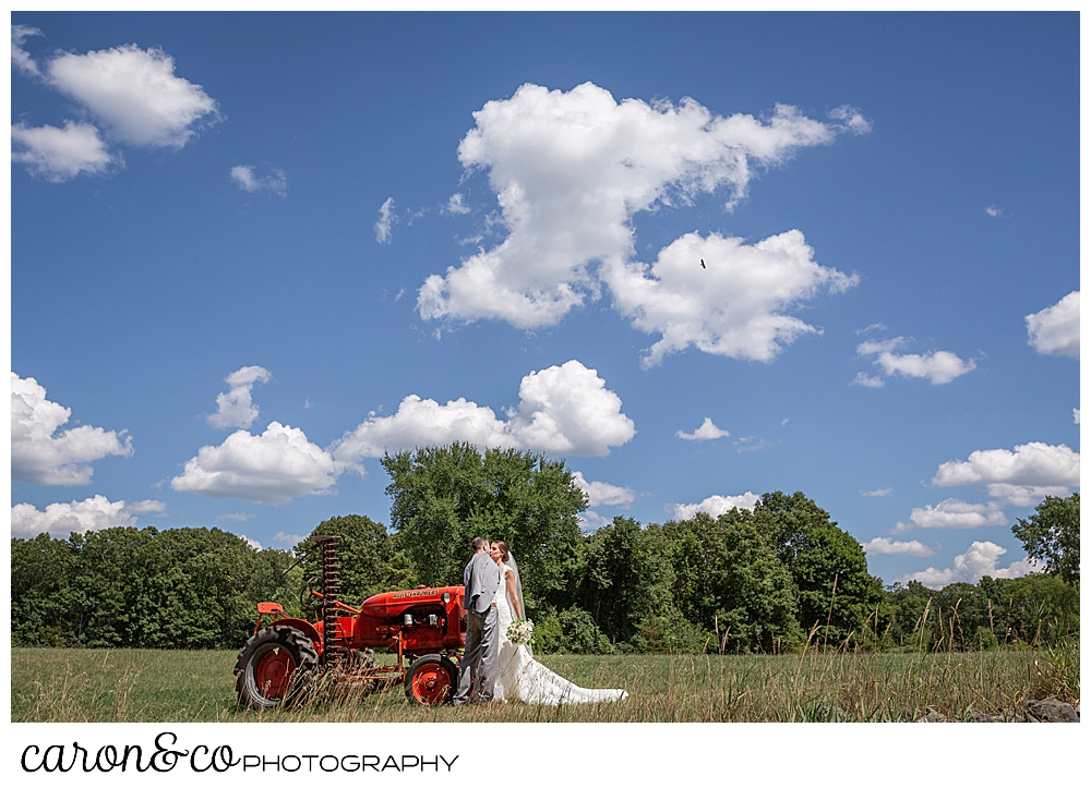 sweet summertime wedding day in rhode island, bride and groom kissing next to an orange tractor in a field