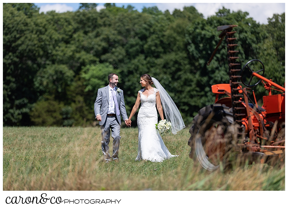 sweet summertime wedding photo of a bride and groom walking hand in hand in a field, next to an orange tractor