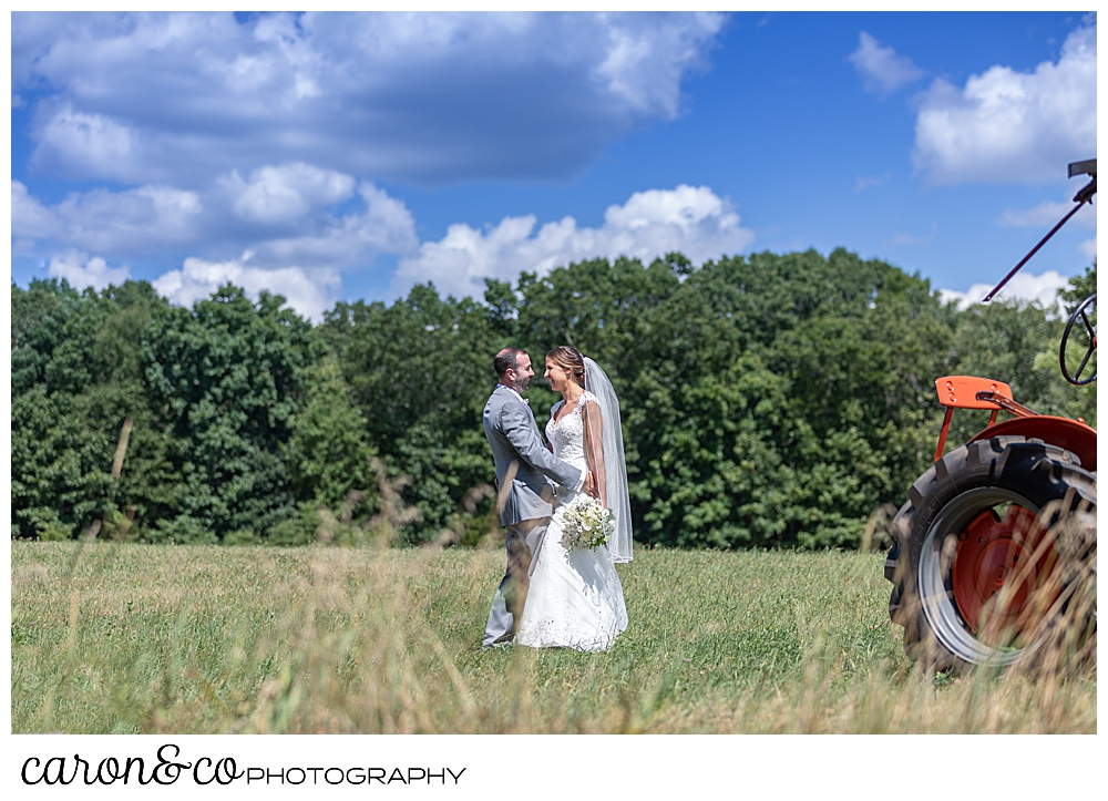 sweet summertime wedding bride and groom kissing in a field near an orange tractor