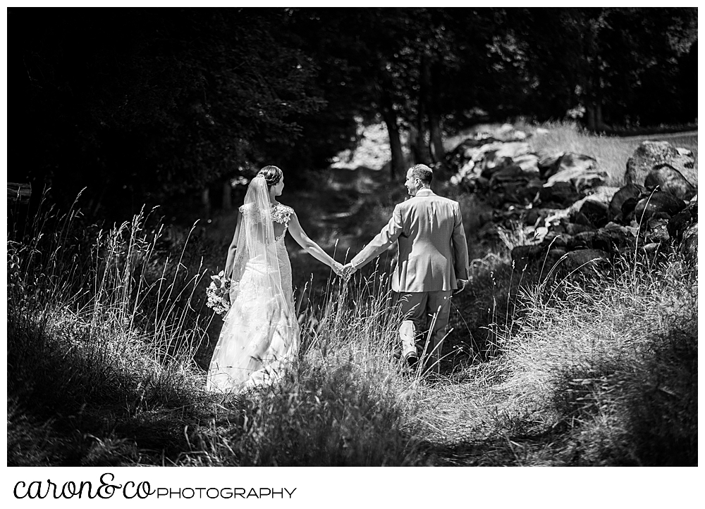 sweet summertime wedding day black and white photo of a bride and groom walking down a grassy lane holding hands