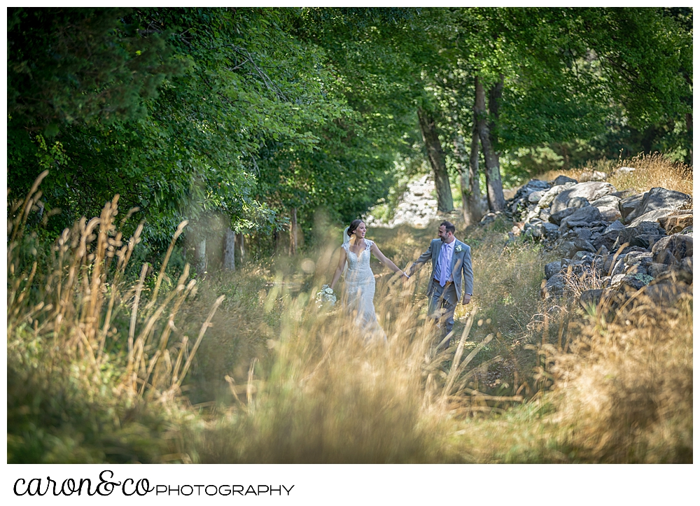 sweet summertime wedding day bride and groom walk hand in hand in a field