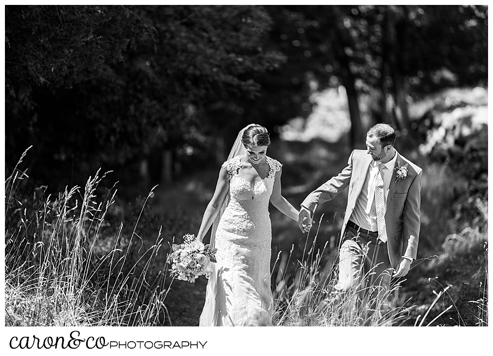 sweet summertime wedding in rhode island, black and white photo of bride and groom walking and holding hands in a grassy field