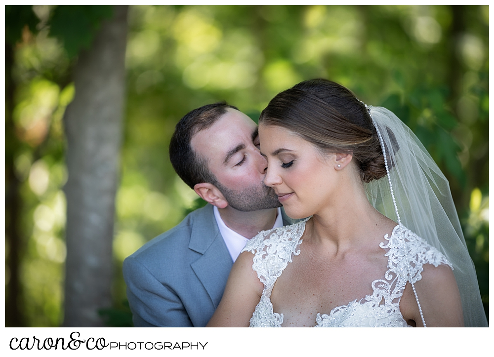 sweet summertime wedding in new england, groom is kissing the bride on her cheek