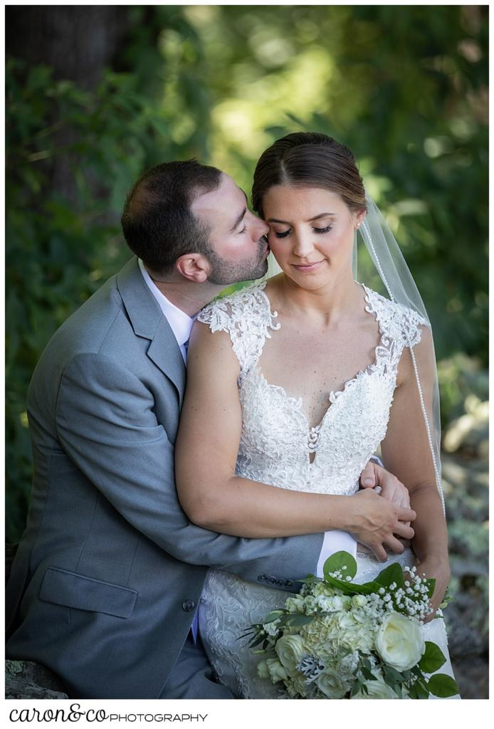 sweet summertime wedding photo with bride sitting on the groom's lap, while he kisses her cheek