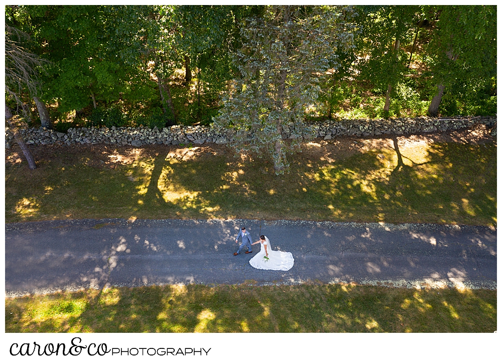 sweet summertime drone wedding photo of a bride and groom walking hand in hand on a shady drive