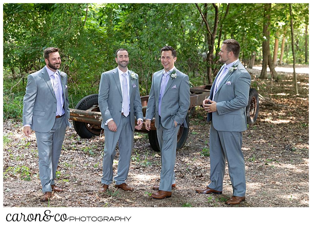sweet summertime wedding photo of groom and groomsmen laughing