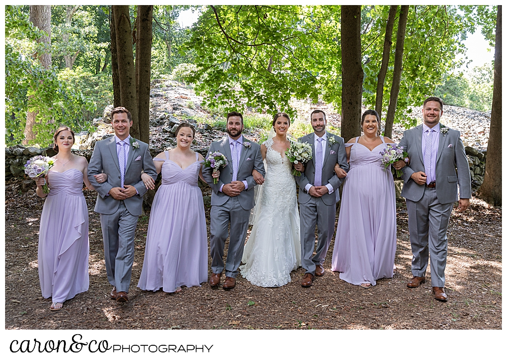 sweet summertime wedding photo of a bridal party linking arms