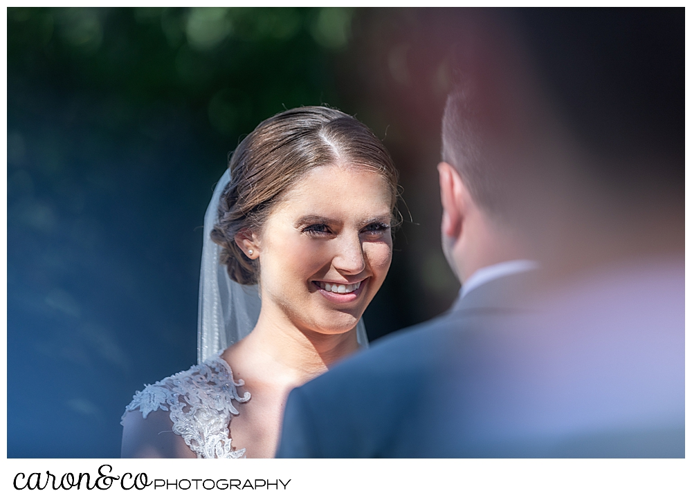 sweet summertime wedding ceremony photo of the bride smiling at the groom