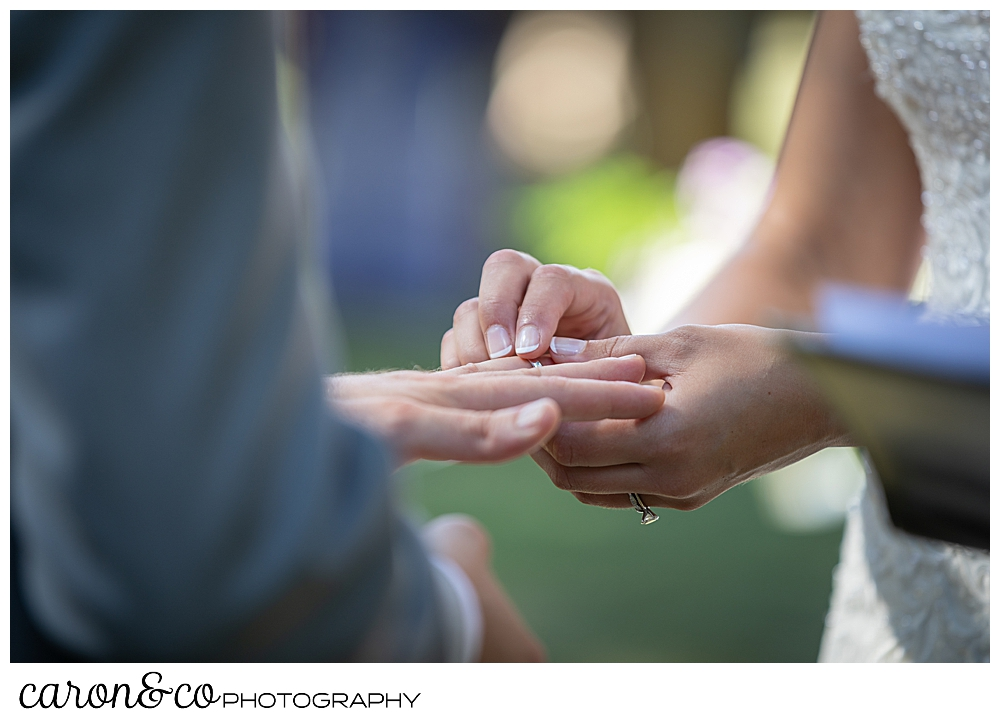 sweet summertime wedding ceremony photo of the bride putting the wedding band on the grooms finger