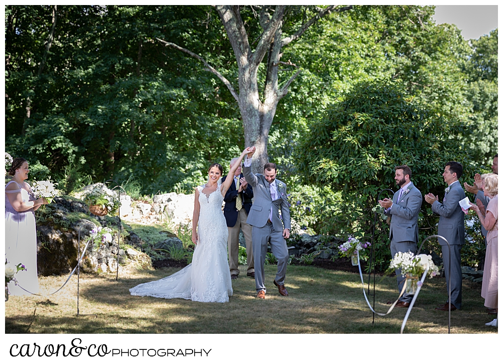 sweet summertime wedding ceremony photo of the bride and groom facing their guests, hands clasped, arms raised