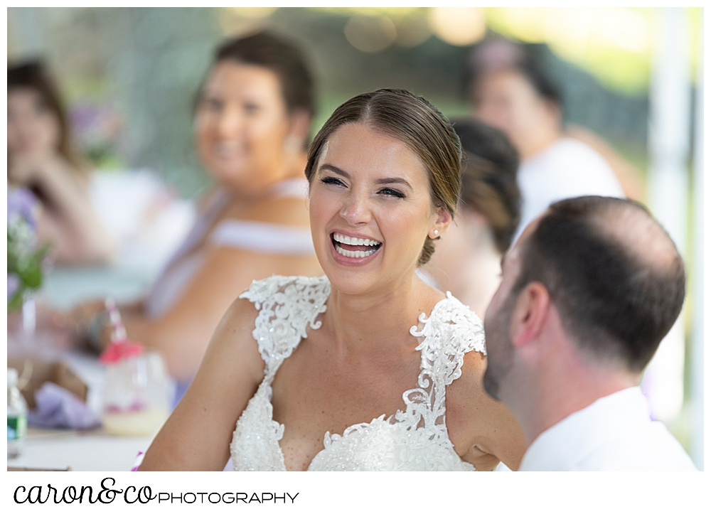 sweet summertime wedding reception photo of the bride laughing during the toasts