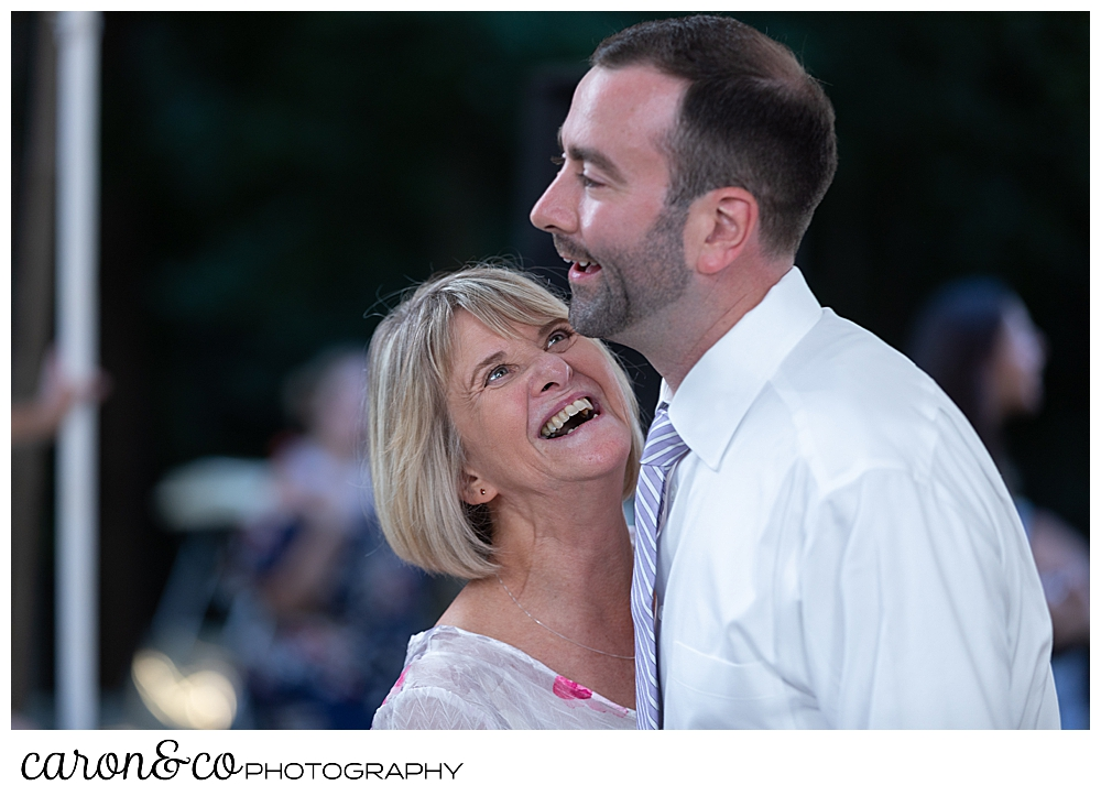 sweet summertime wedding reception photo of groom and his mother dancing and laughing