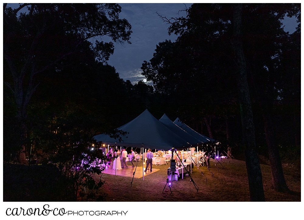 sweet summertime wedding reception photo of a tented reception after dark