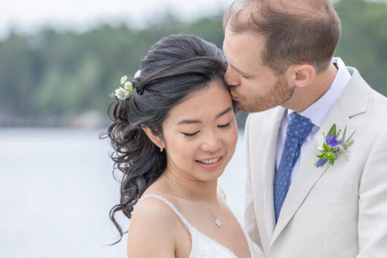 groom kissing bride's forehead duringGrey Havens Inn, Georgetown Maine wedding