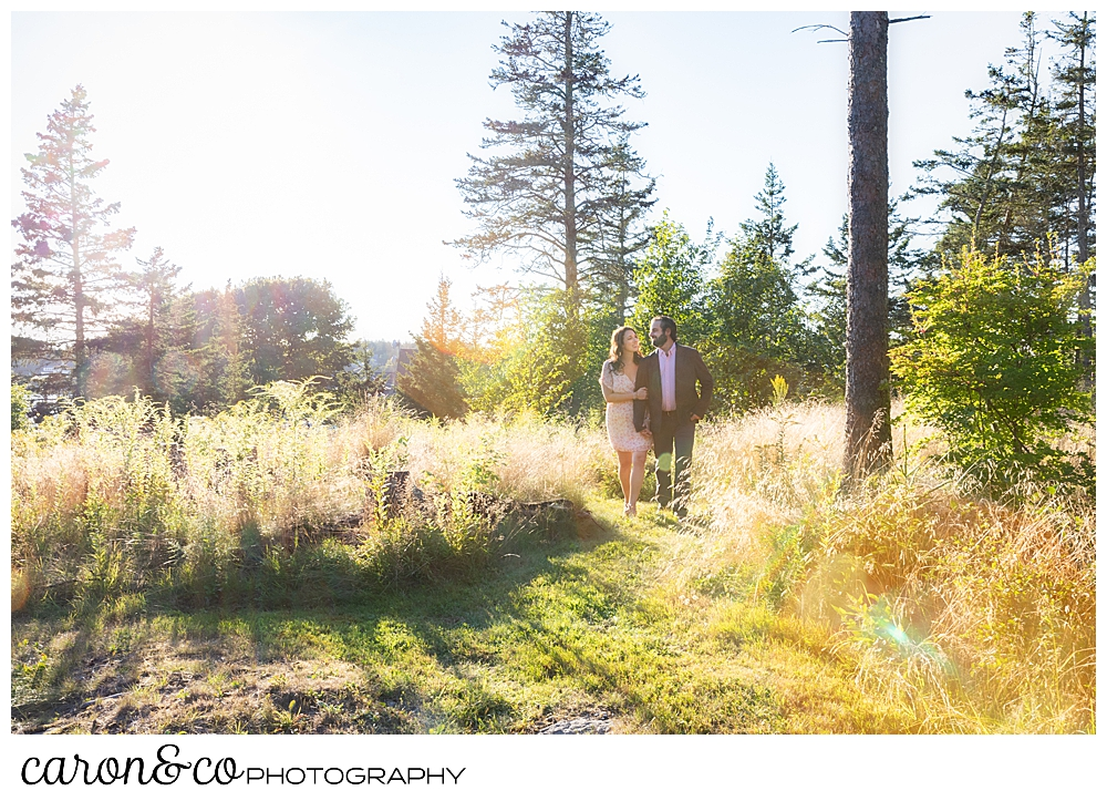 a woman and man walk together in a field with the sun behind them, during a Midcoast Maine engagement