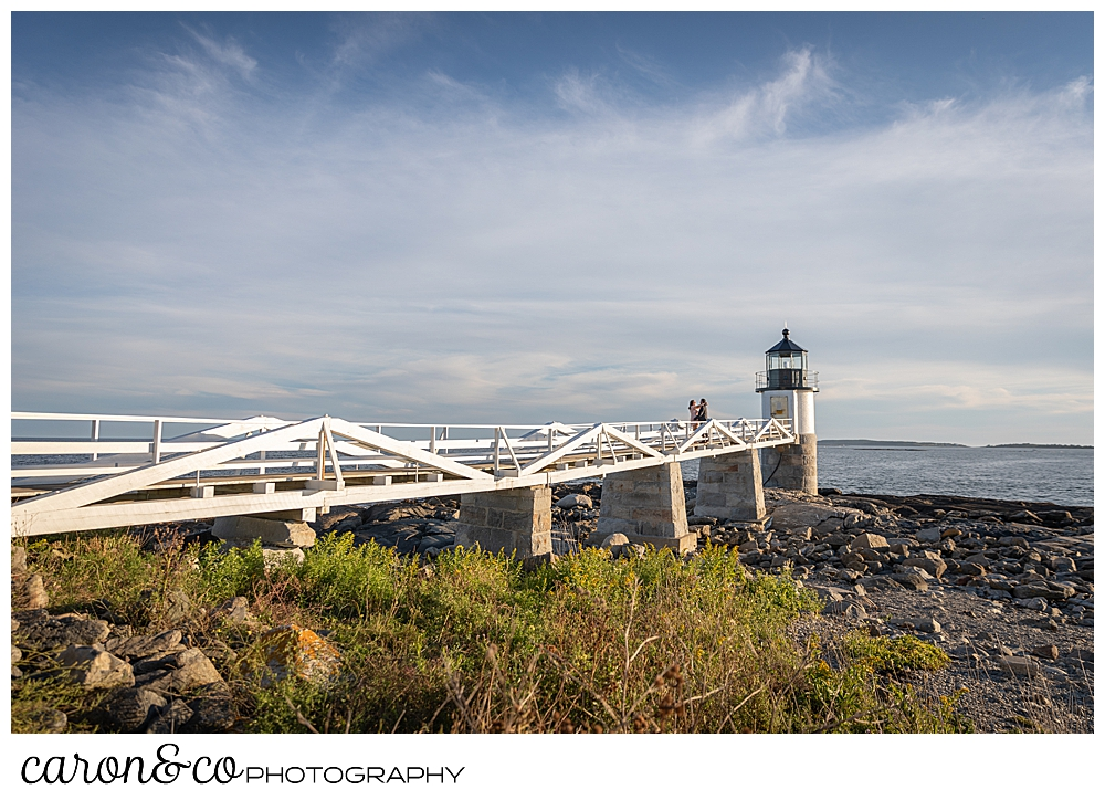 a woman and man are walking toward Marshall Point Lighthouse during their Port Clyde Maine engagement photo session