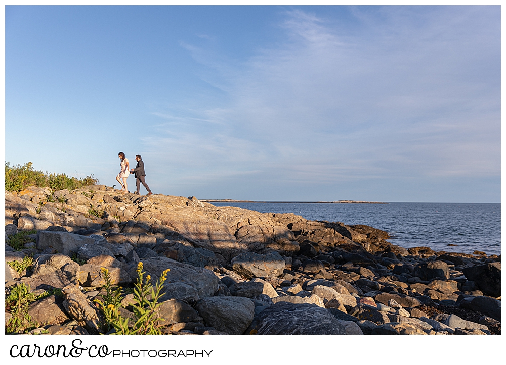 a man and woman are walking on the rocks during their coastal Maine engagement photo session