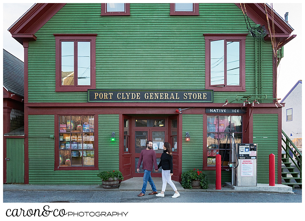 A man and woman are walking hand in hand past the Port Clyde General Store, during their Port Clyde Maine engagement