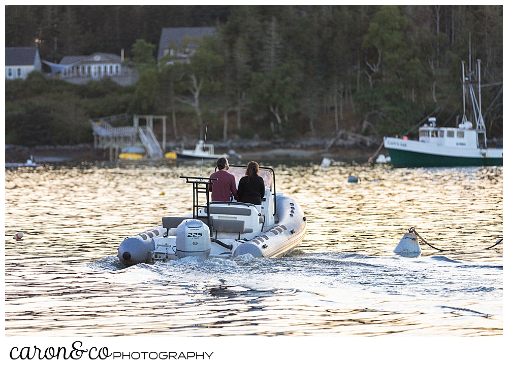 a man and a woman with their backs to the camera, are moving away in a brig inflatable boat, during their Port Clyde engagement photos