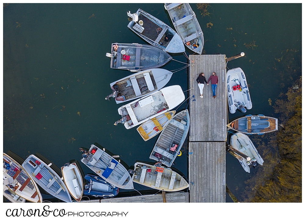 a man and woman are lying on a dock in a Maine drone engagement photo, during their Port Clyde Maine engagement
