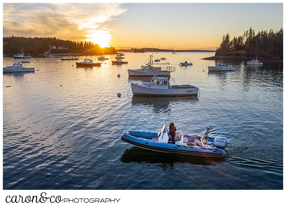 a man and a woman are driving a Brig inflatable boat during sunset, at their Port Clyde Maine engagment