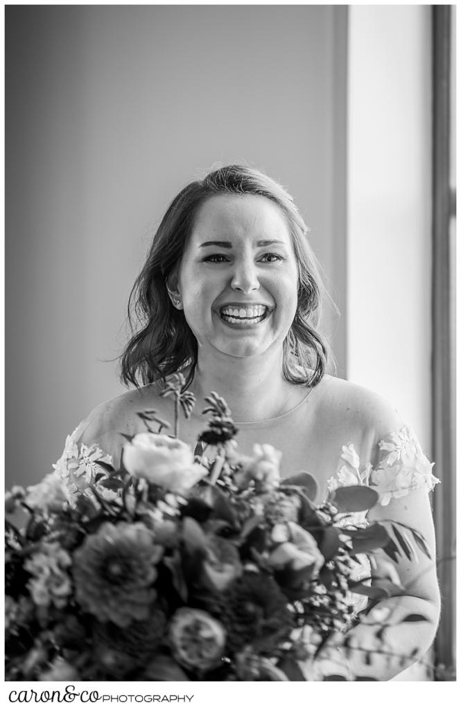 black and white photo of a bride laughing as she holds her bouquet