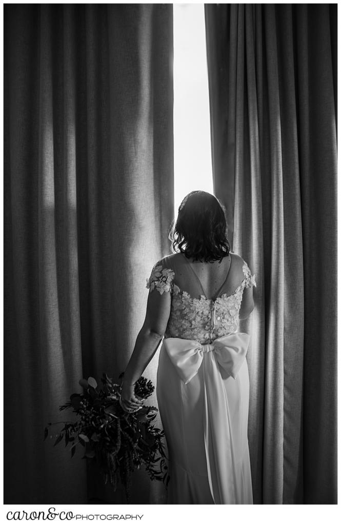 a black and white photo of a bride looking out between two drapes in a hotel room
