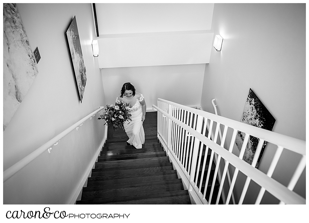 a black and white photo of a bride walking up the stairs to her ceremony at a Portland Press Hotel wedding