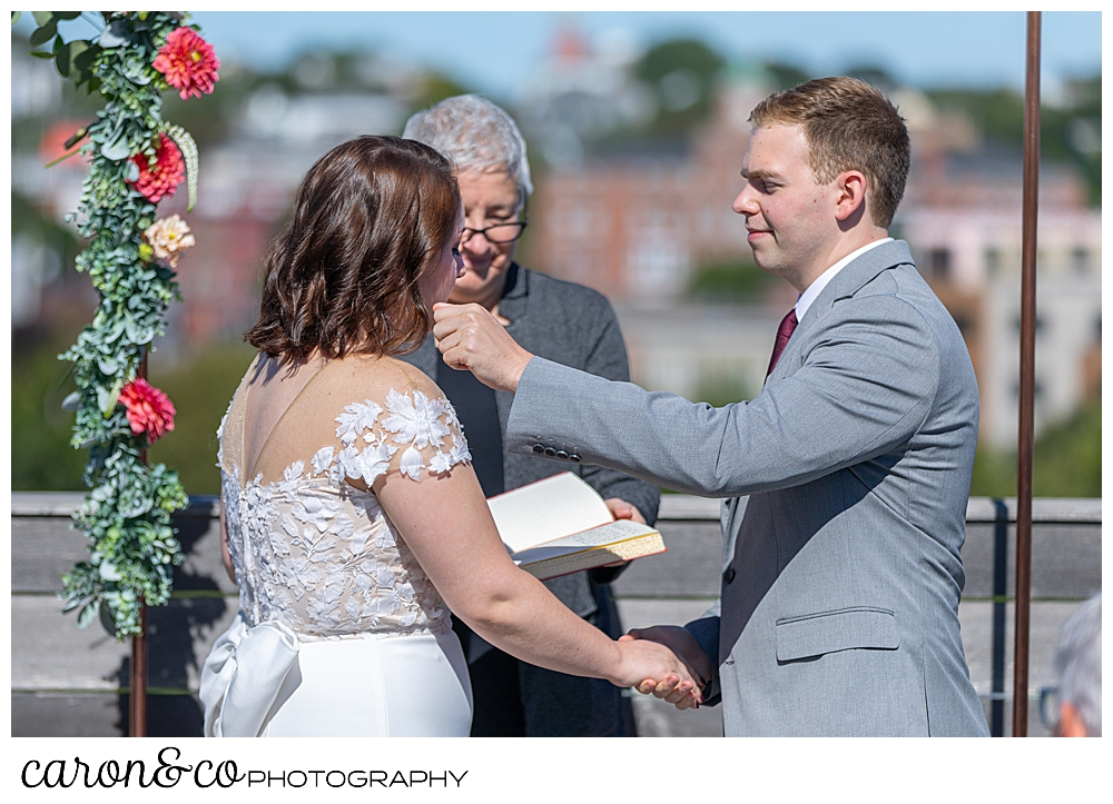 a groom reaches out to wipe a tear from his bride's cheek