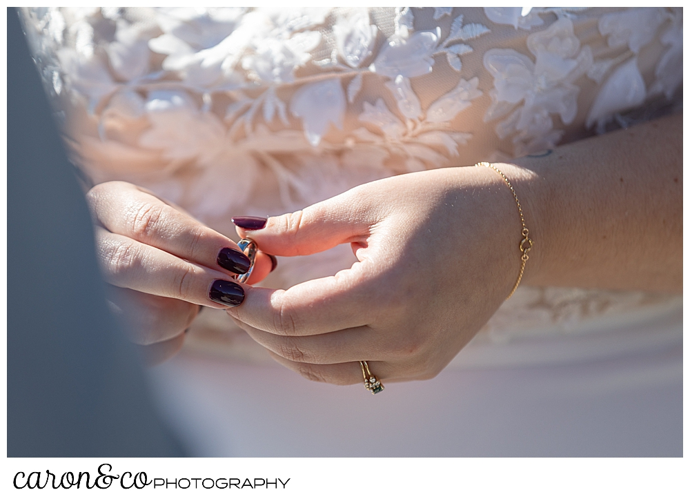 a bride holds the grooms wedding band just before putting it on his finger