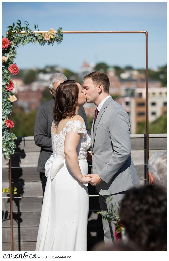 bride and groom's first kiss on the rooftop of their Portland Press Hotel wedding ceremony