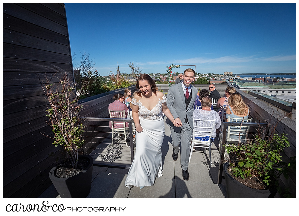 bride and groom during their recessional at their Portland Press Hotel wedding ceremony