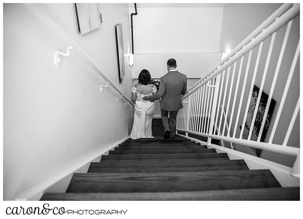 black and white photo of a bride and groom going down the stairs after their Portland Press Hotel wedding