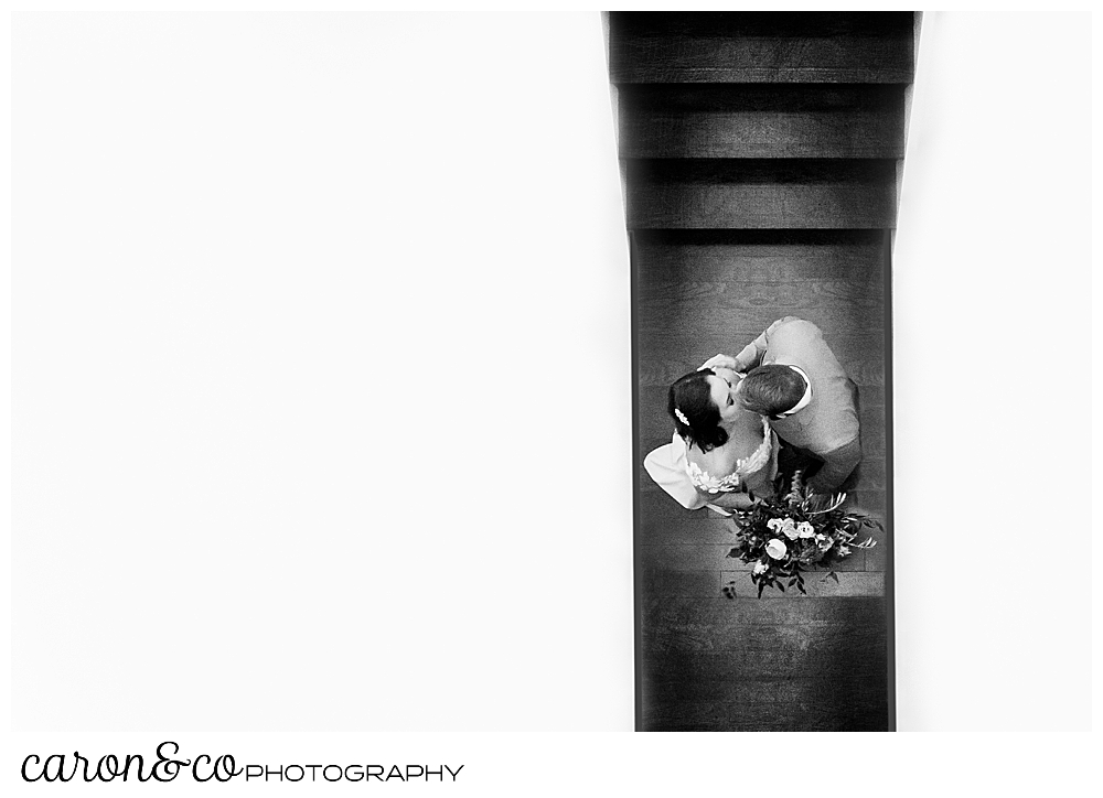 black and white photo of a bride and groom kissing at the bottom of the stairway at their Portland Press Hotel wedding