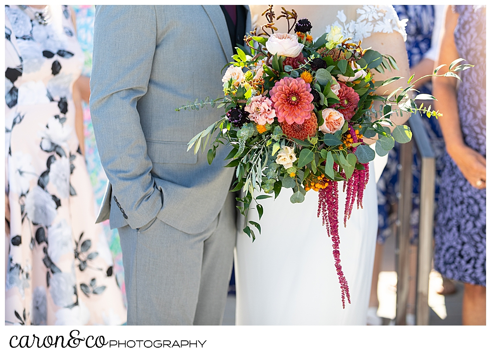 a bride and groom stand together among their guests, the bride's bouquet is the subject of the photo, flowers by Harmon's Floral Company