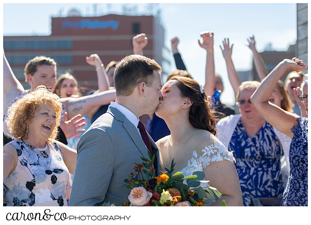 a bride and groom kiss while their guests cheer at a Portland Press Hotel wedding