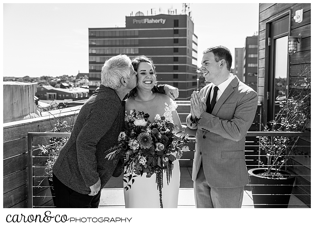 the officiant and relative of the bride, kisses the bride while the groom looks on from the rooftop of their Portland Press Hotel wedding