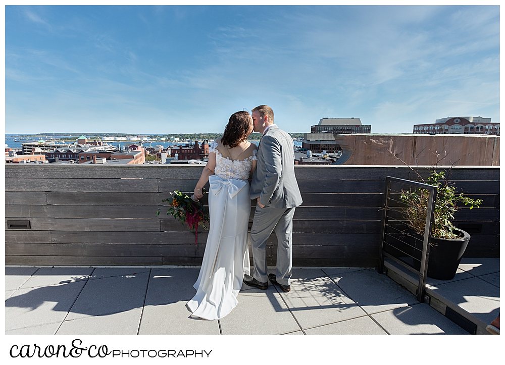 a bride and groom kiss on the rooftop of their Portland Press Hotel wedding